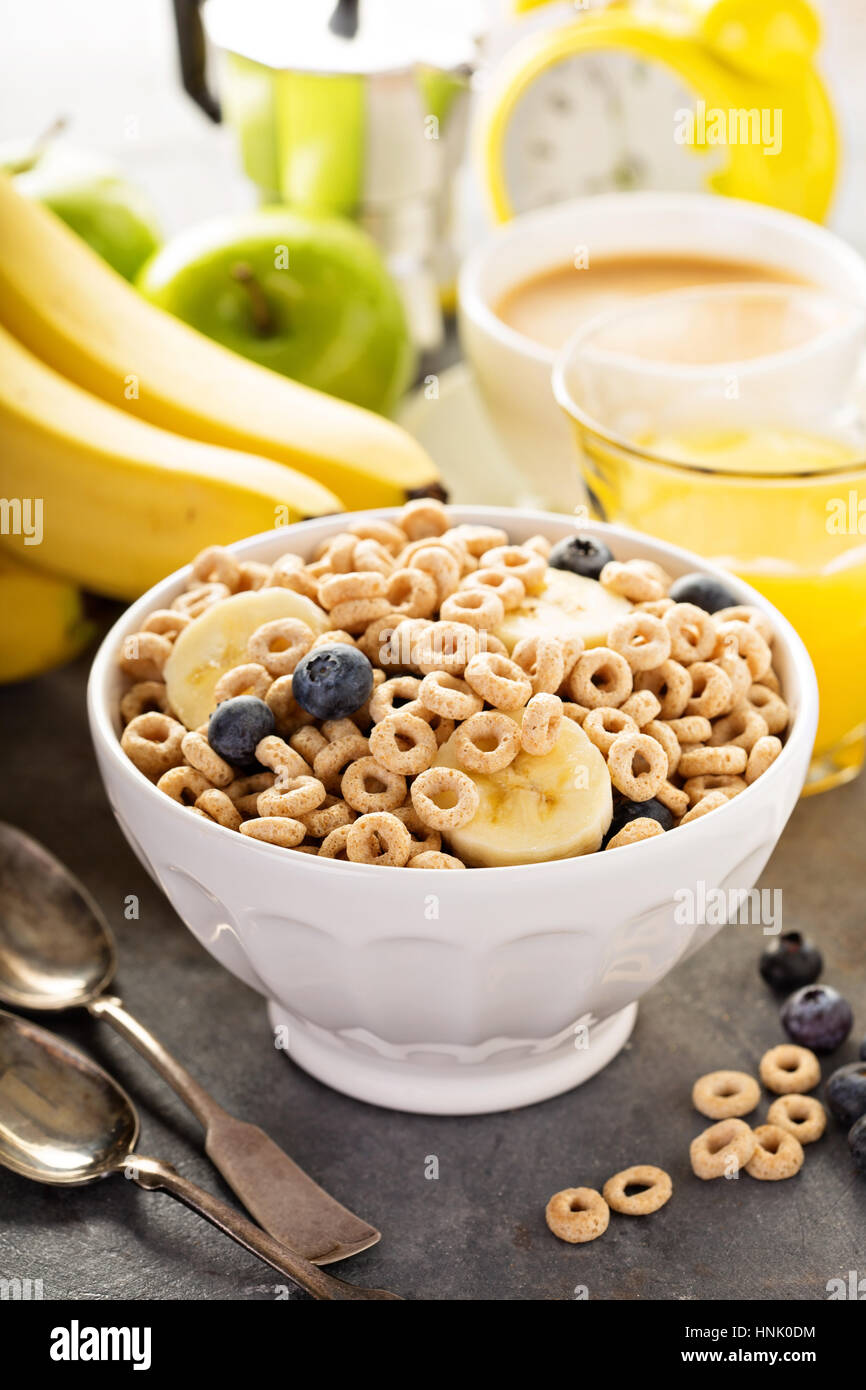 Healthy cold cereal with banana and blueberry in a white bowl, quick breakfast or snack for children - Stock Image