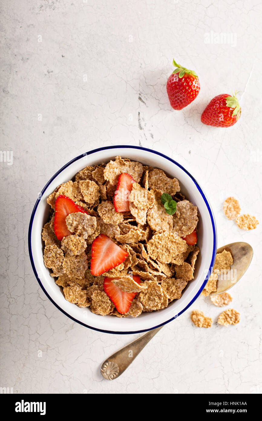 Multigrain wholewheat healthy cereals with fresh berry for breakfast overhead shot on white - Stock Image