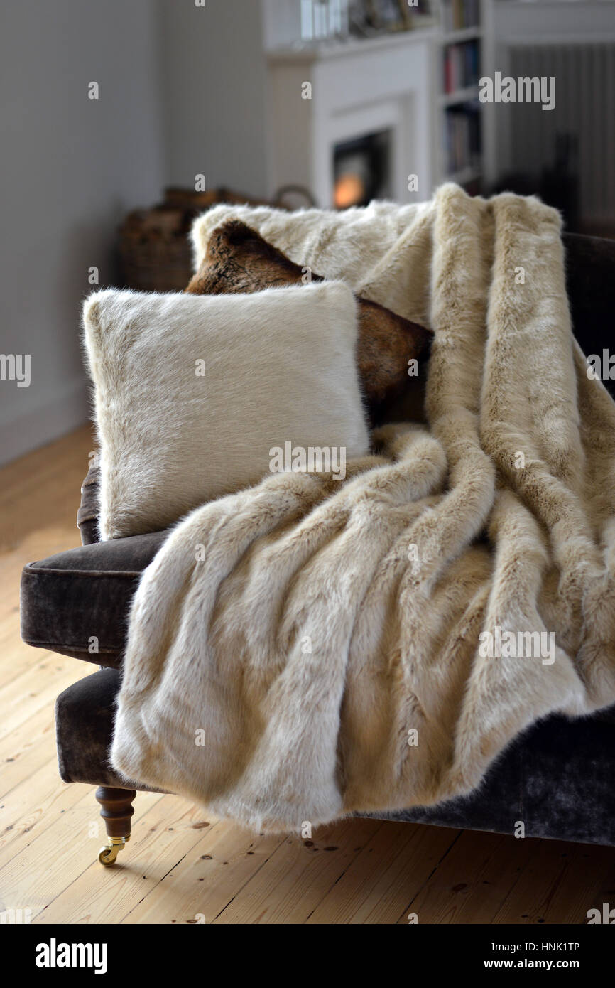 Faux fur throws and cushions room interior - Stock Image