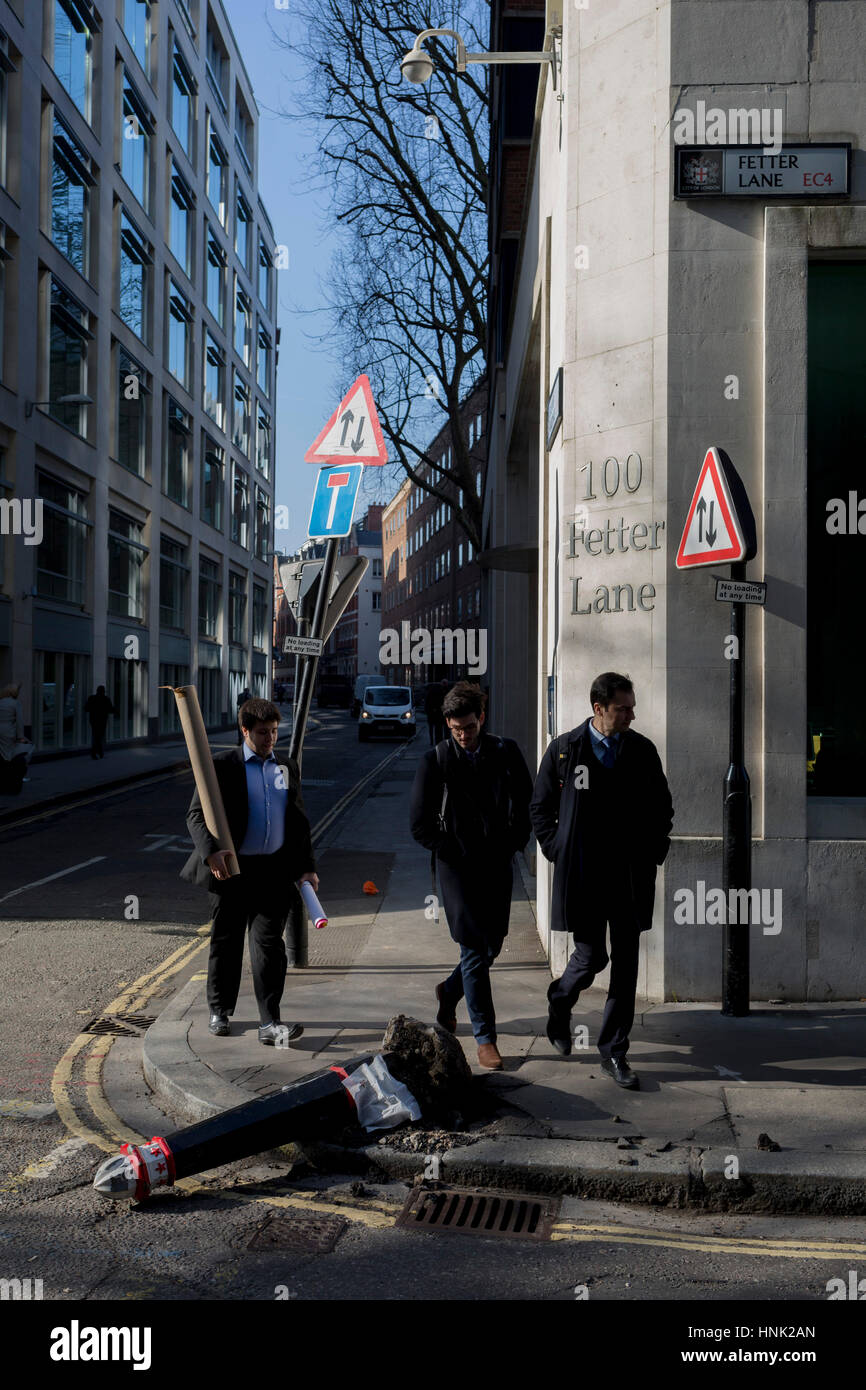 Young men walk past a damaged bollard, knocked over by a vehicle on 13th February 2017, in the City of London, United - Stock Image