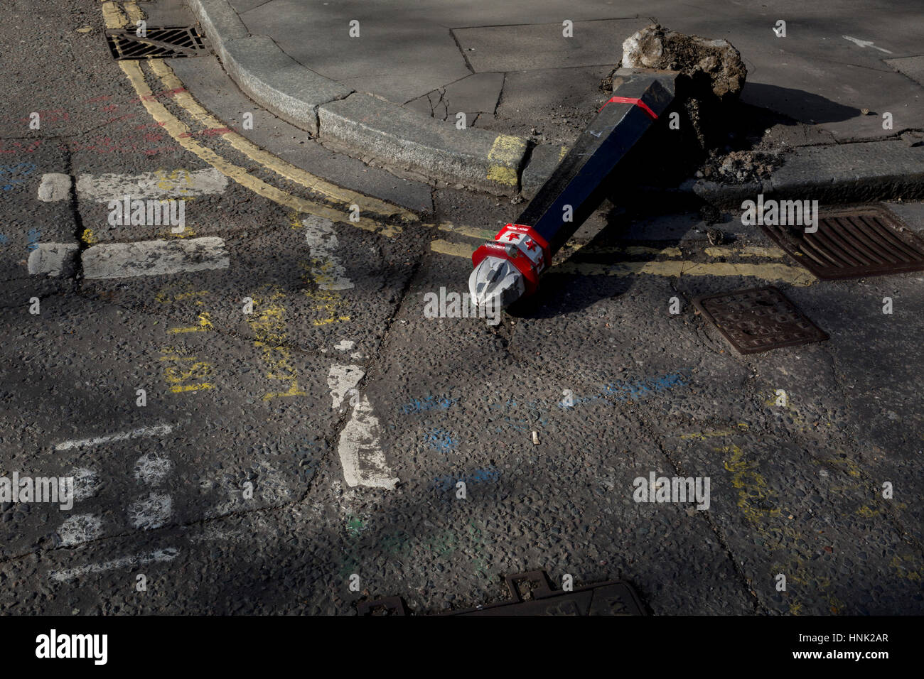 A detail of the road surface where a damaged bollard lies horizontal, knocked over by a vehicle on 13th February - Stock Image