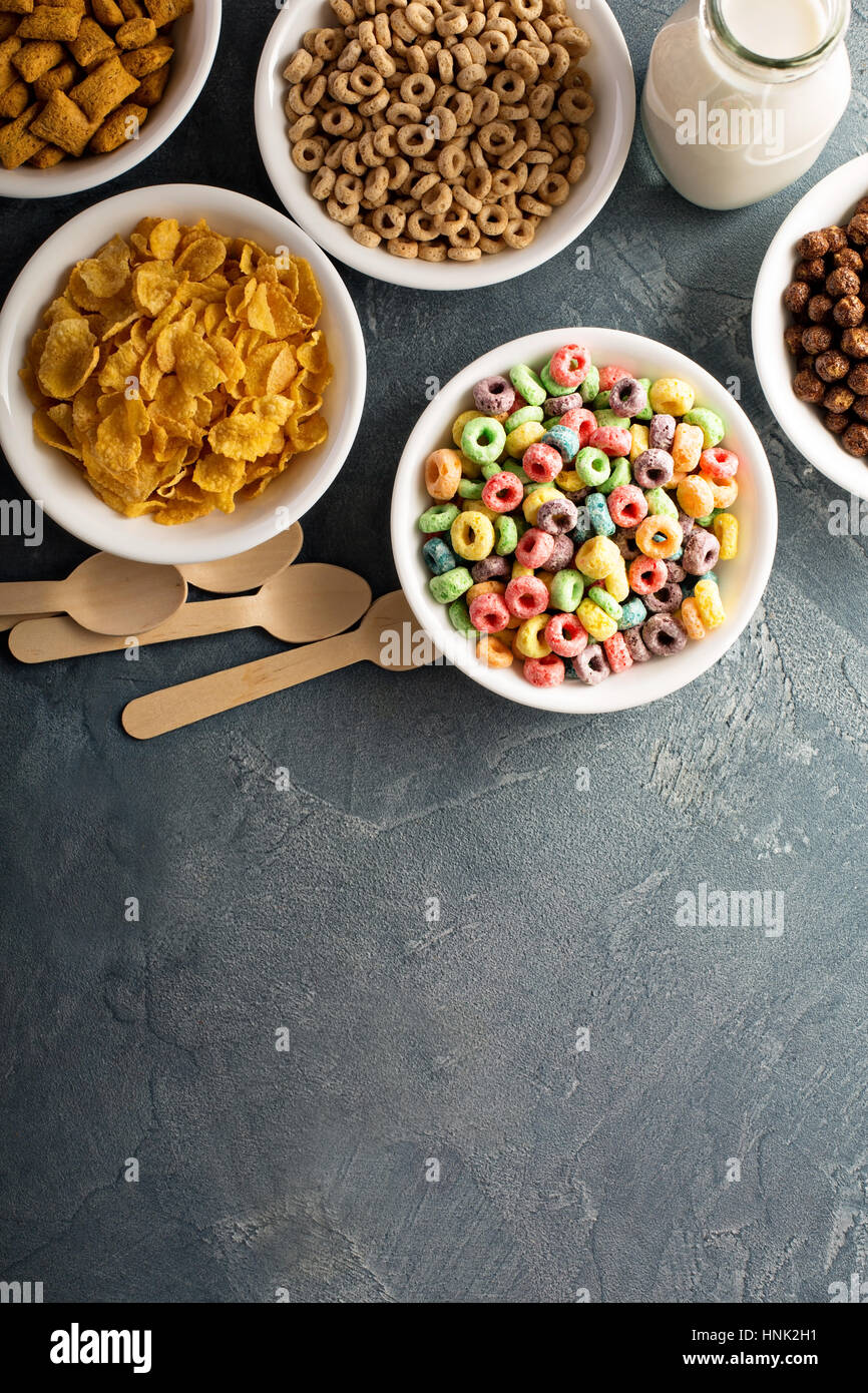 Variety of cold cereals in white bowls, quick breakfast for kids overhead shot with copyspace - Stock Image