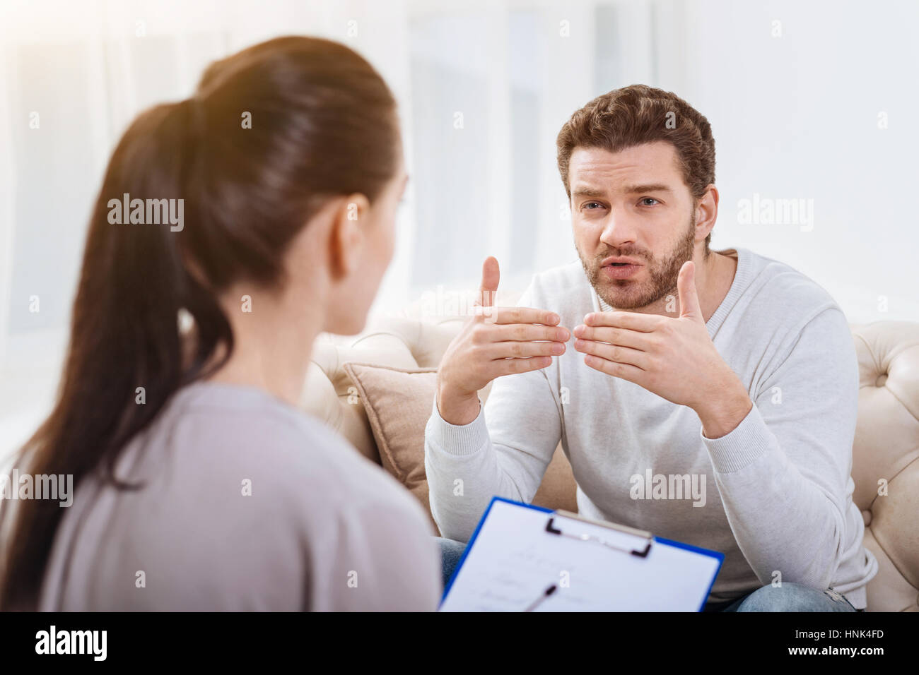 Nice bearded man talking to the psychologist - Stock Image