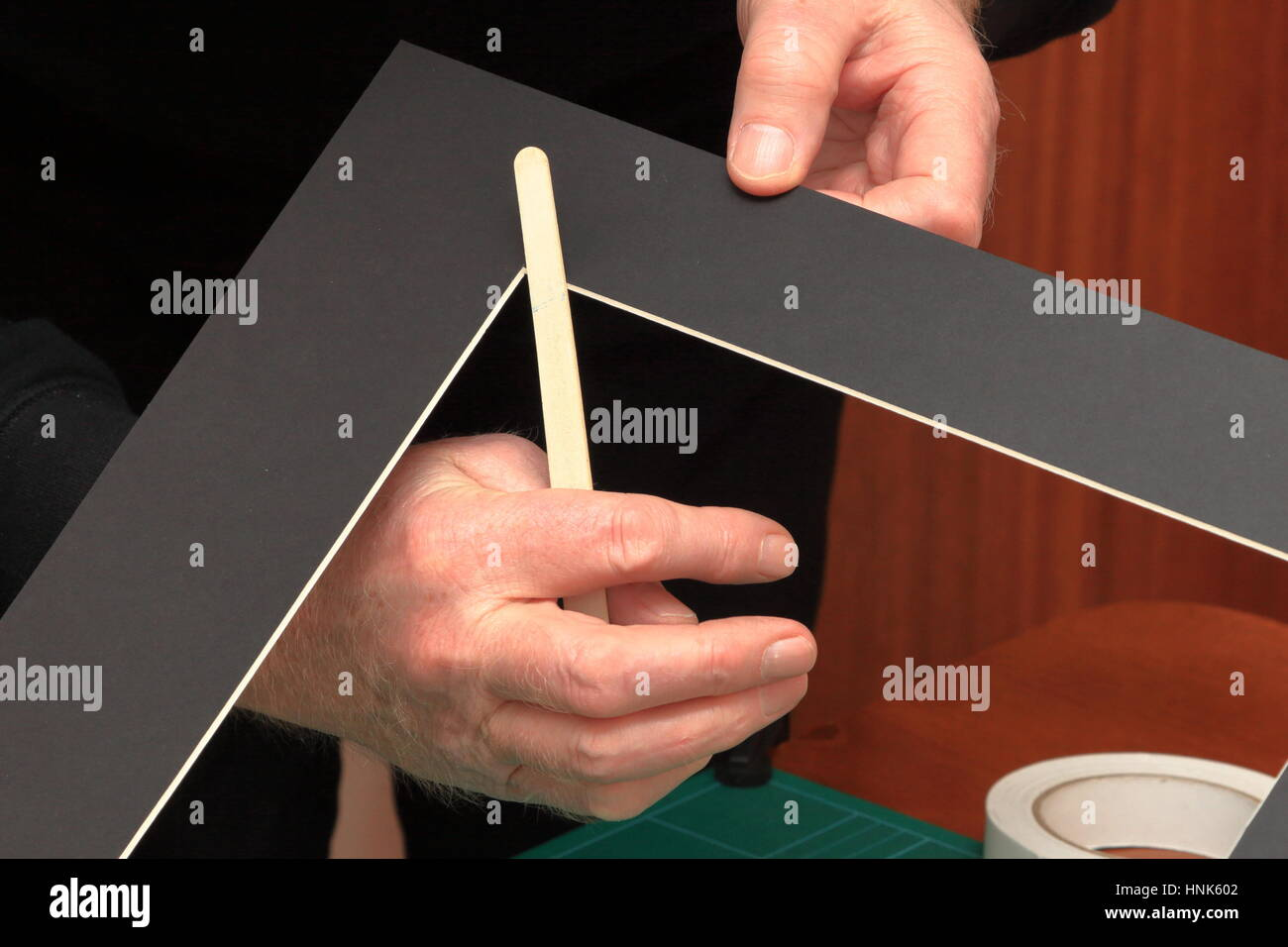 Using a common nail emery board to carefully tidy up small imperfections in the corners of a freshly cut picture - Stock Image
