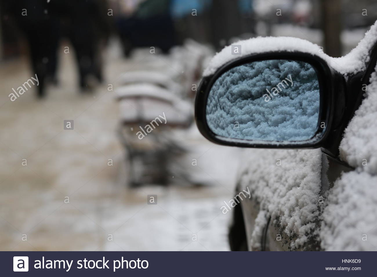 A car mirror and seats covered in snow after a heavy winter snowfall in downtown Budapest, Hungary - Stock Image