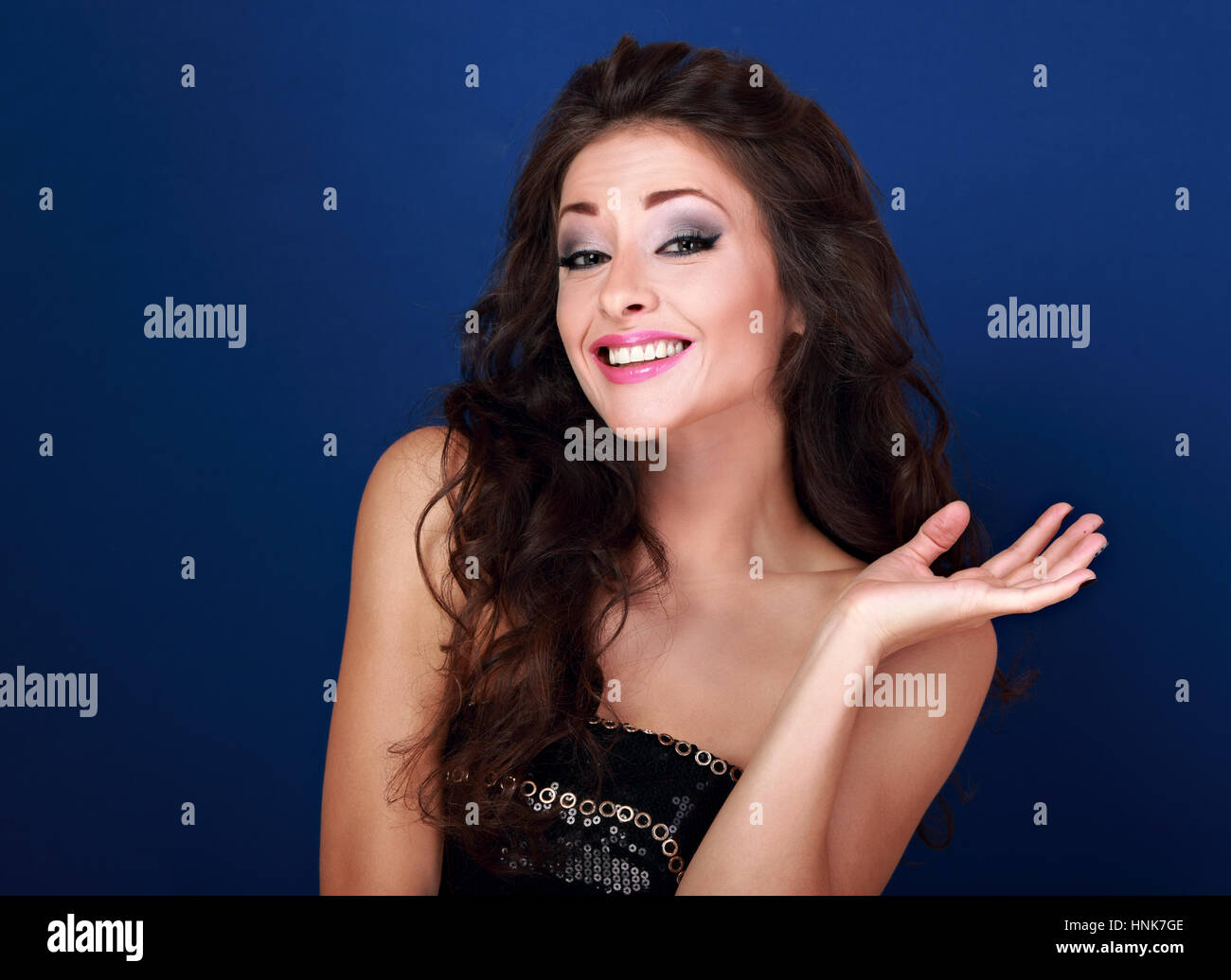 Excited beautiful makeup woman grimacing and showing oops sign her hand on blue background. Closeup portrait - Stock Image
