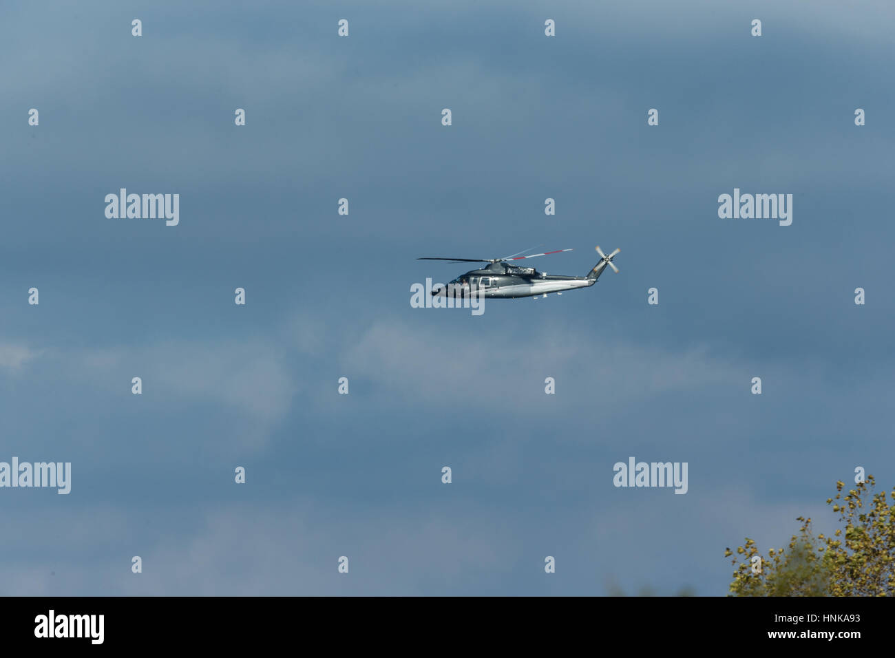 Private helicopter flying by with a cloudy sky in the background Stock Photo