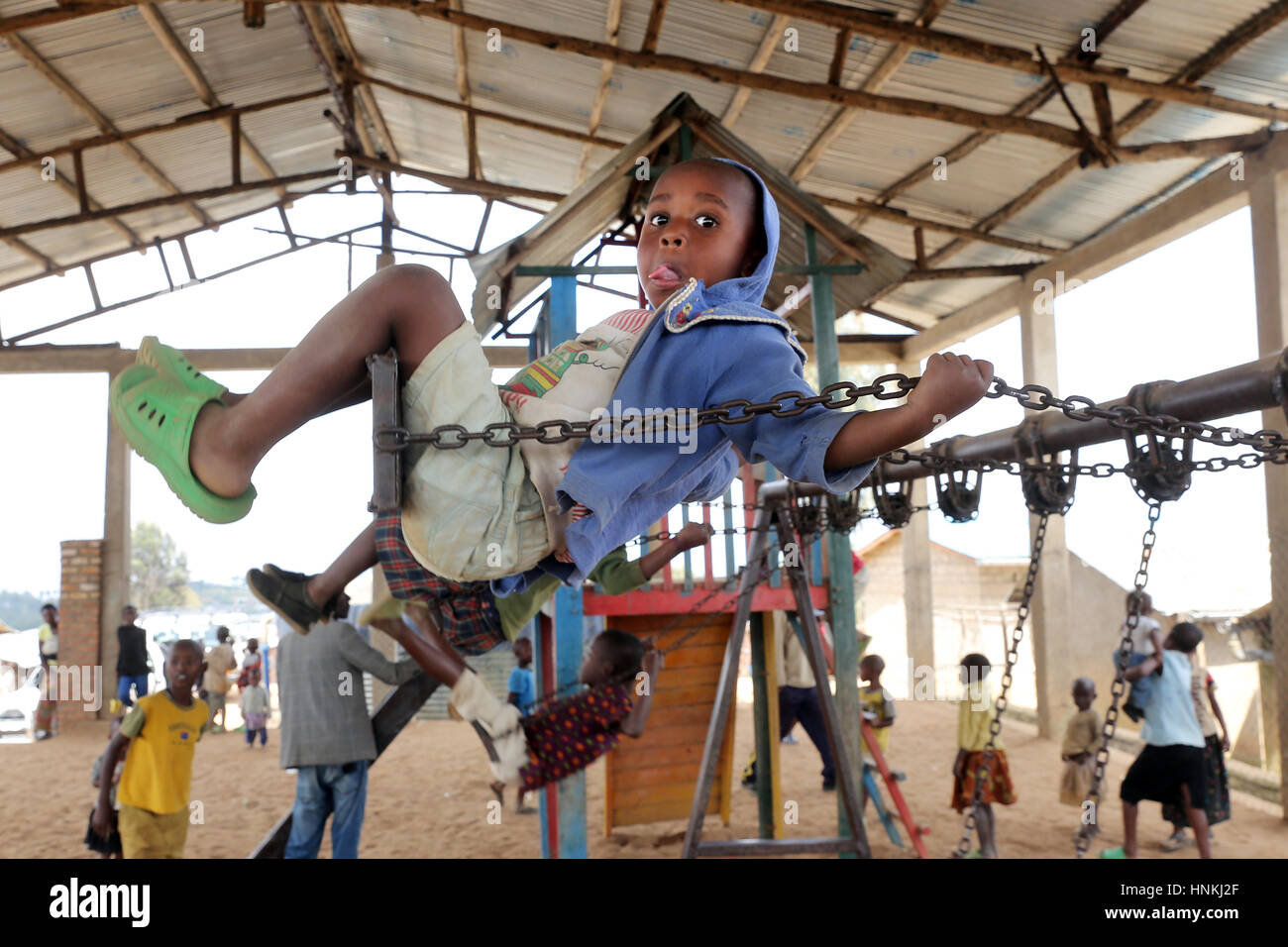 Boy on a swing, children's playground in the refugee camp Kigeme, diocese of Gikongoro, Rwanda, Africa - Stock Image