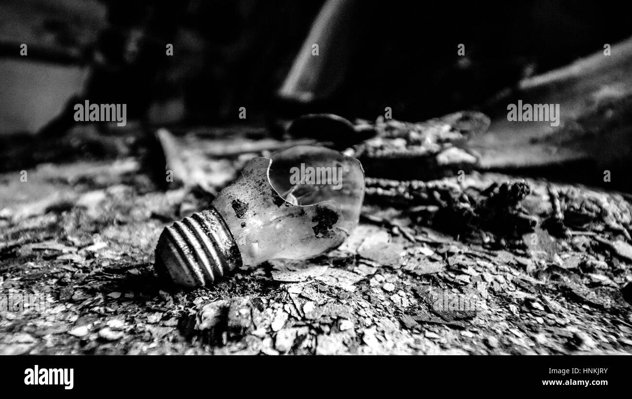 destroyed and dirty bulb laying on a burned surface. Relationship break up. Single. House on fire. - Stock Image