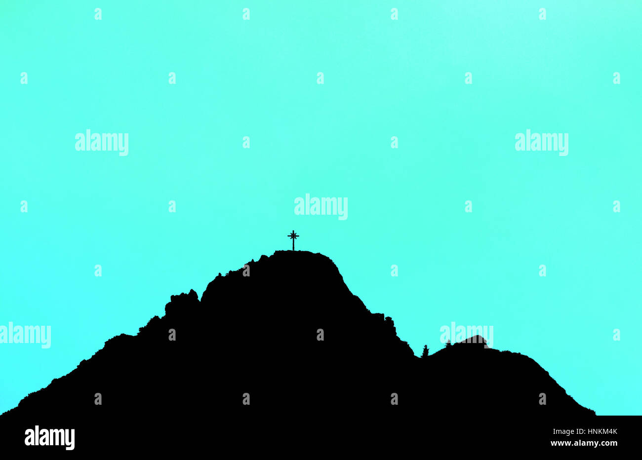 Black silhouette of mountain peak with summit cross. Cyan background. - Stock Image