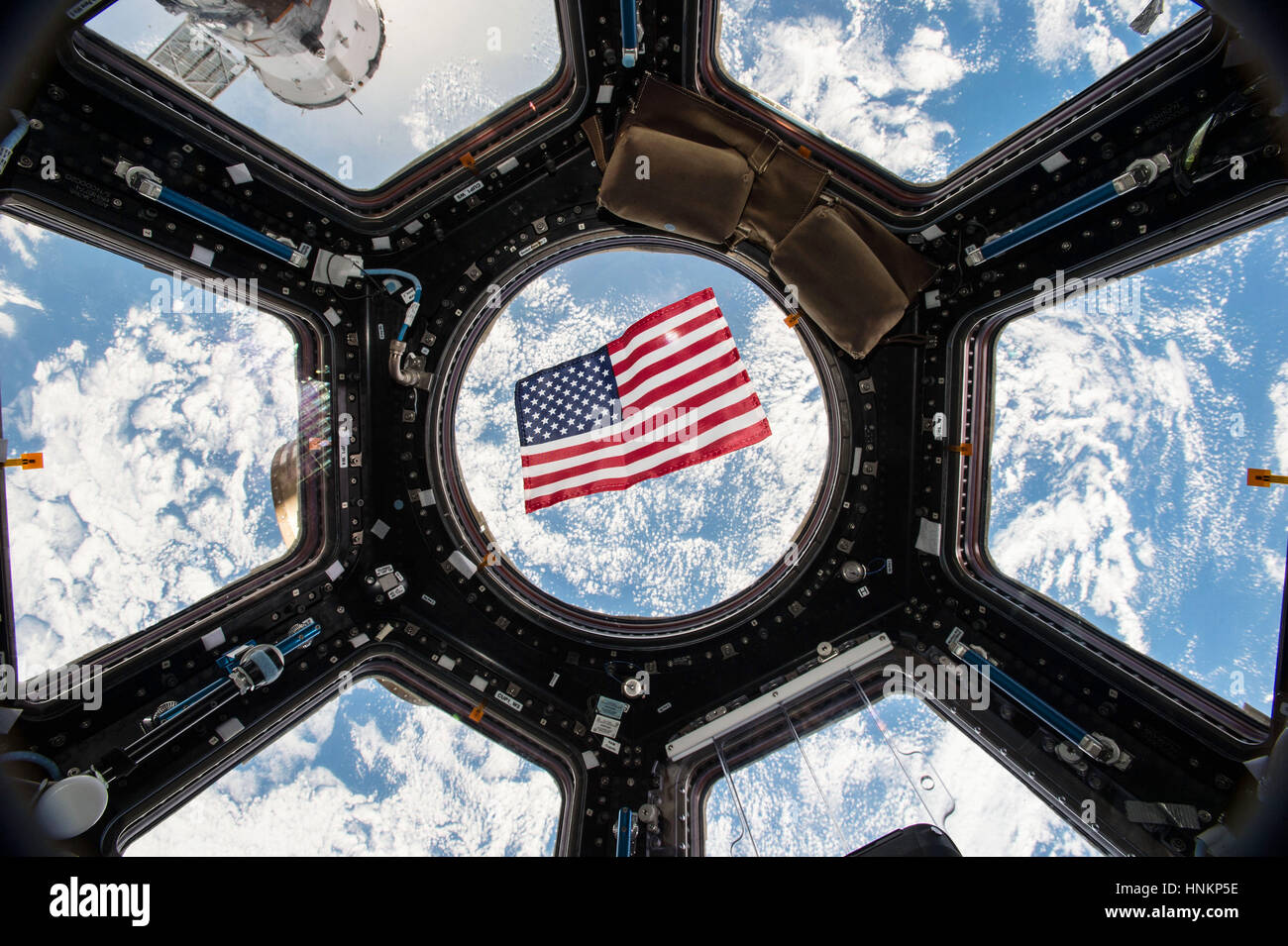 American flag is visible in the windows of the cupola aboard the International Space Station - Stock Image