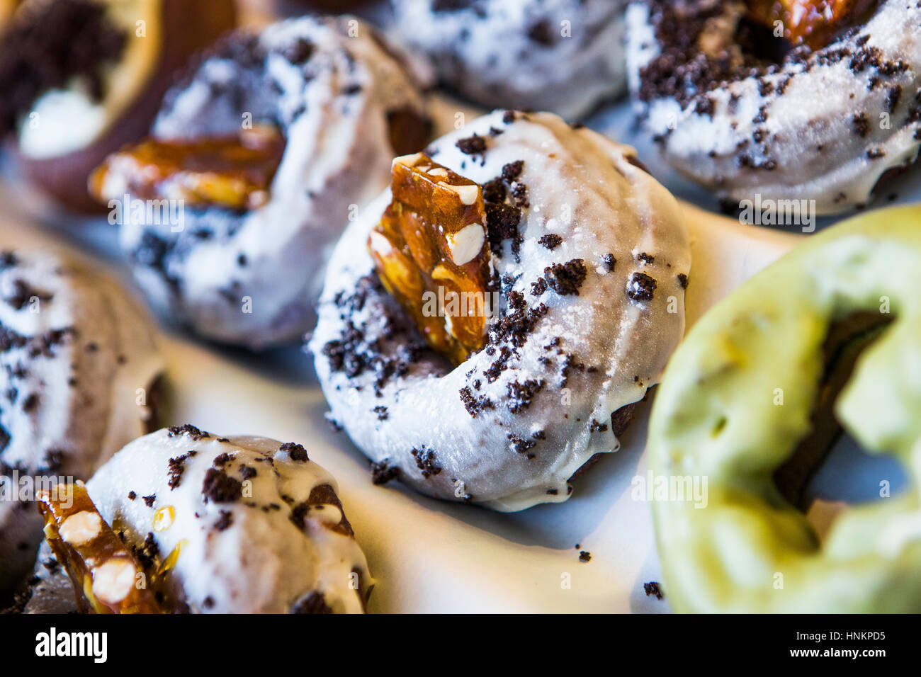 Glazed doughnuts with nut brittle on sale on food stall. - Stock Image