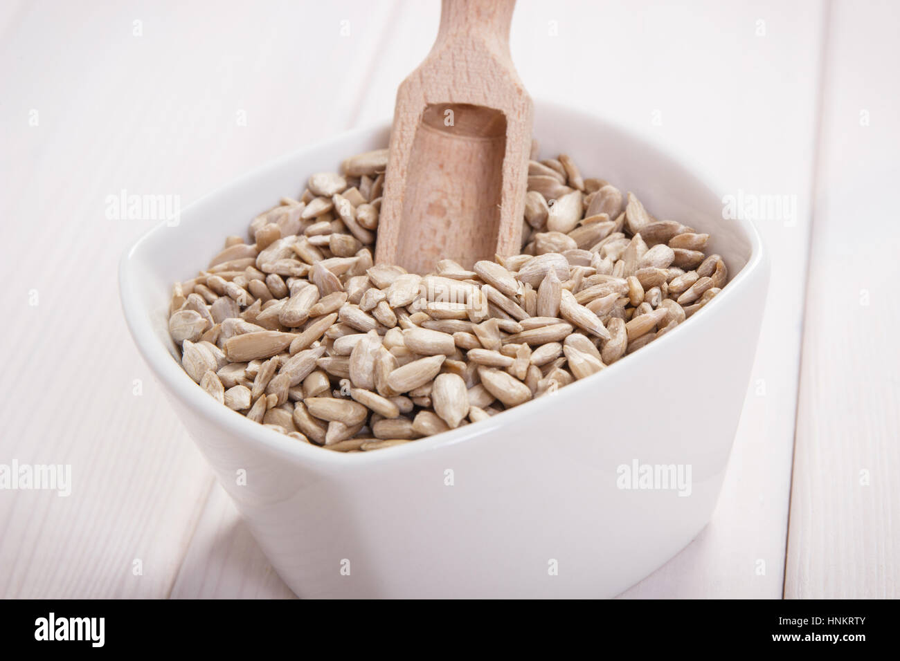 White bowl with sunflower seeds containing zinc and dietary fiber on white boards, natural sources of minerals, - Stock Image