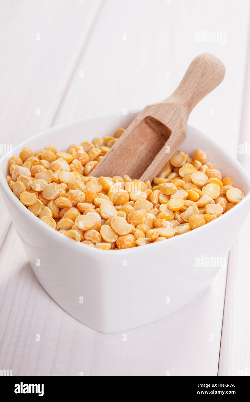 White bowl with split peas containing zinc and dietary fiber on white boards, natural sources of minerals, healthy - Stock Image