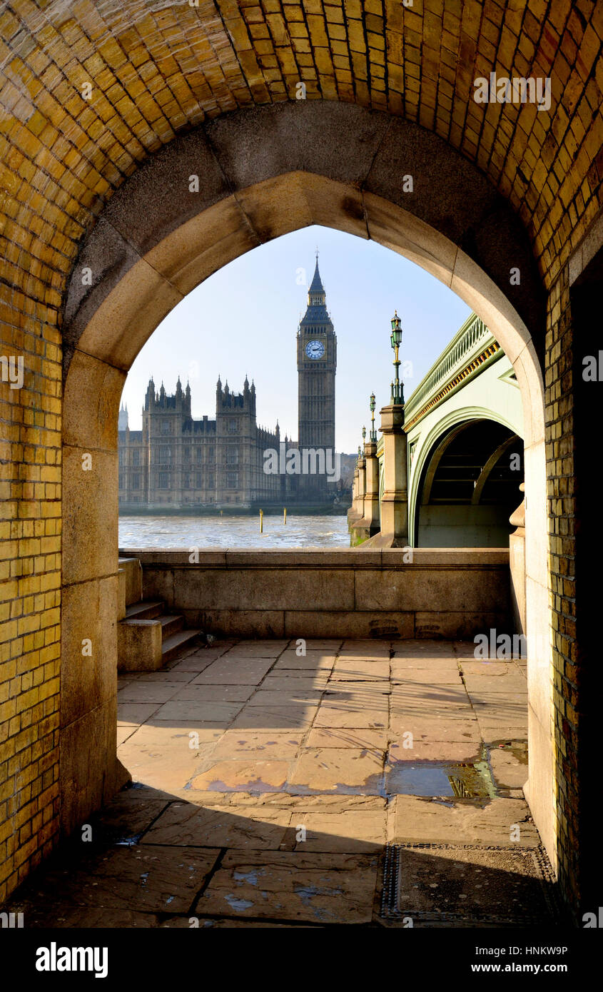 London, England, UK. Big Ben and the Houses of Parliament seen through an arch under Westminster Bridge - Stock Image