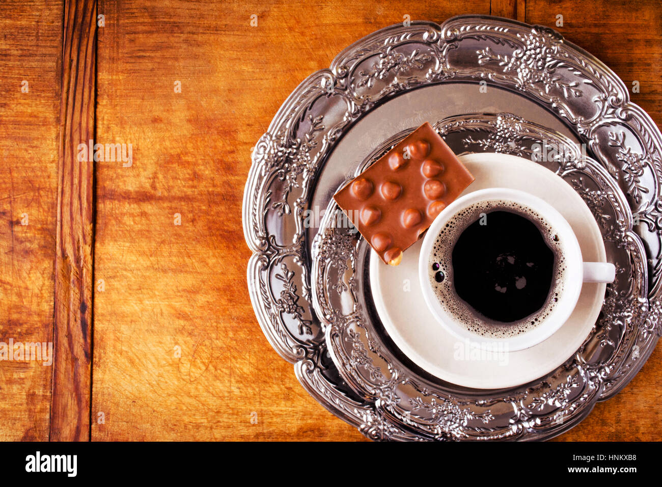 Hot coffee and chocolate bar served on vintage plates on wooden background, top view - Stock Image