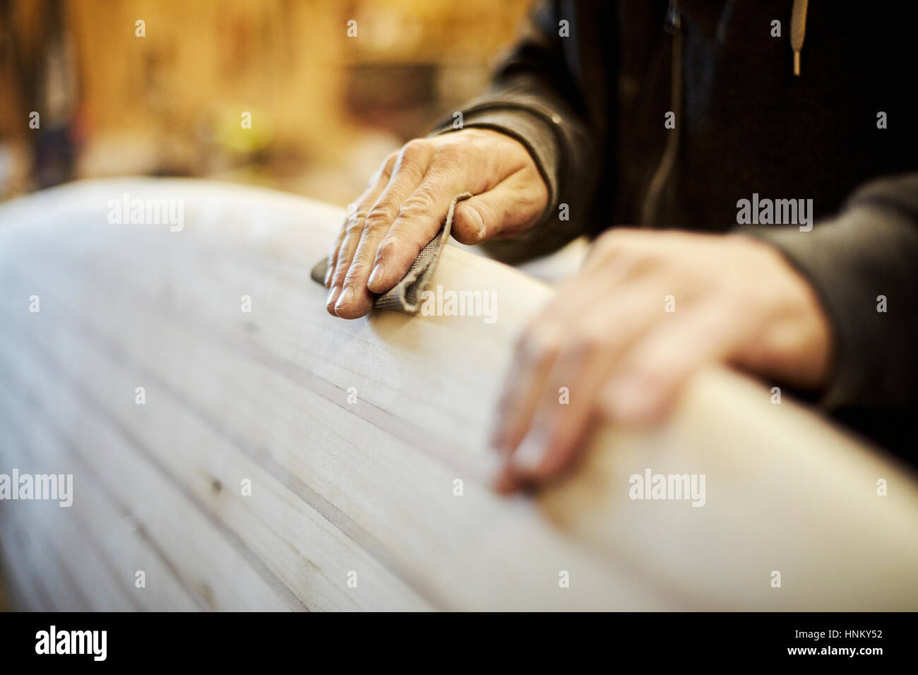 Man standing in a workshop sanding the edge of a wooden surfboard. - Stock Image