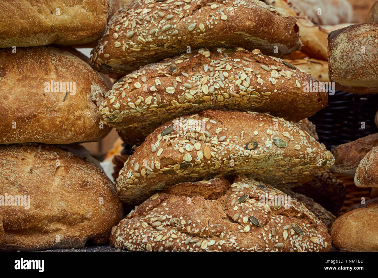 A stack of artisan seeded bread loaves - detail - Stock Image