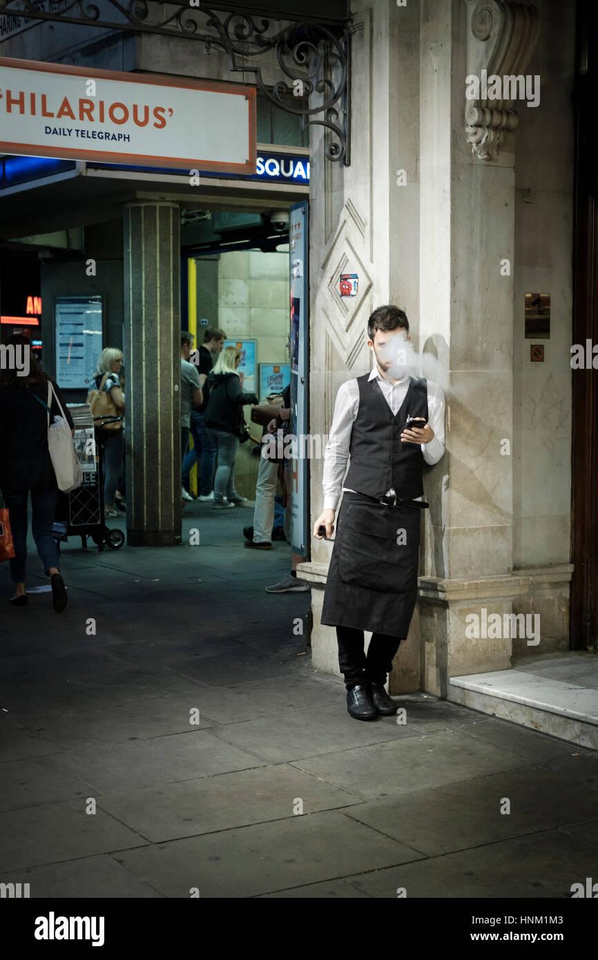 Waiter having cigarette break,Leicester Square Tube Station,Londom,UK - Stock Image