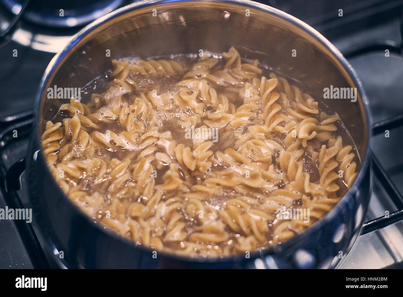 Boiling Wholemeal Pasta cooking in a saucepan on the stove - Stock Image