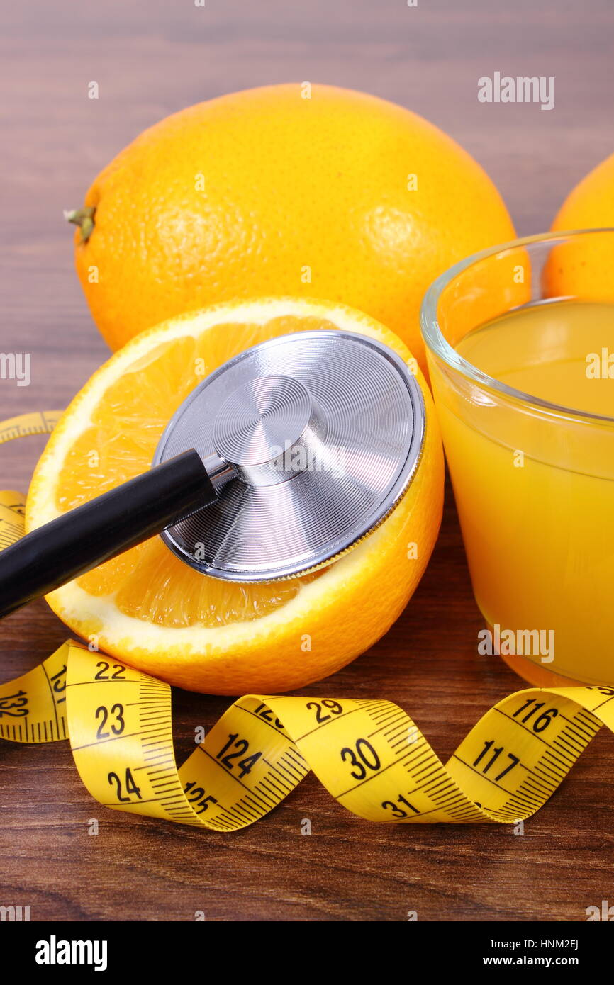 Medical stethoscope, fresh ripe orange, glass of juice and tape measure on wooden surface plank, healthy lifestyles - Stock Image