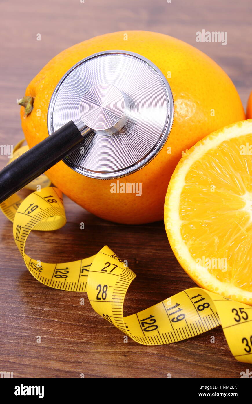 Medical stethoscope and tape measure with fresh ripe orange on wooden surface plank, healthy lifestyles and nutrition - Stock Image