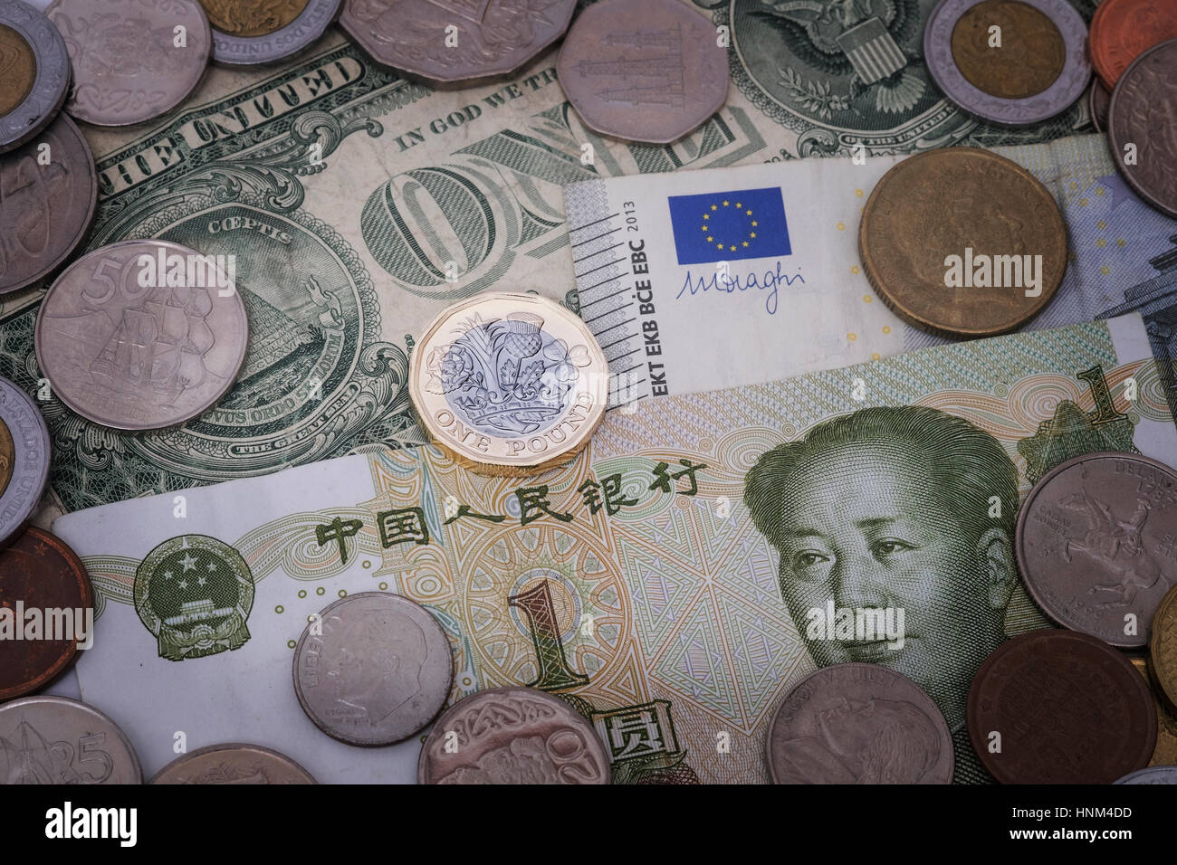 British pound coin against background of currencies including yuan, dollar, and euro - Stock Image