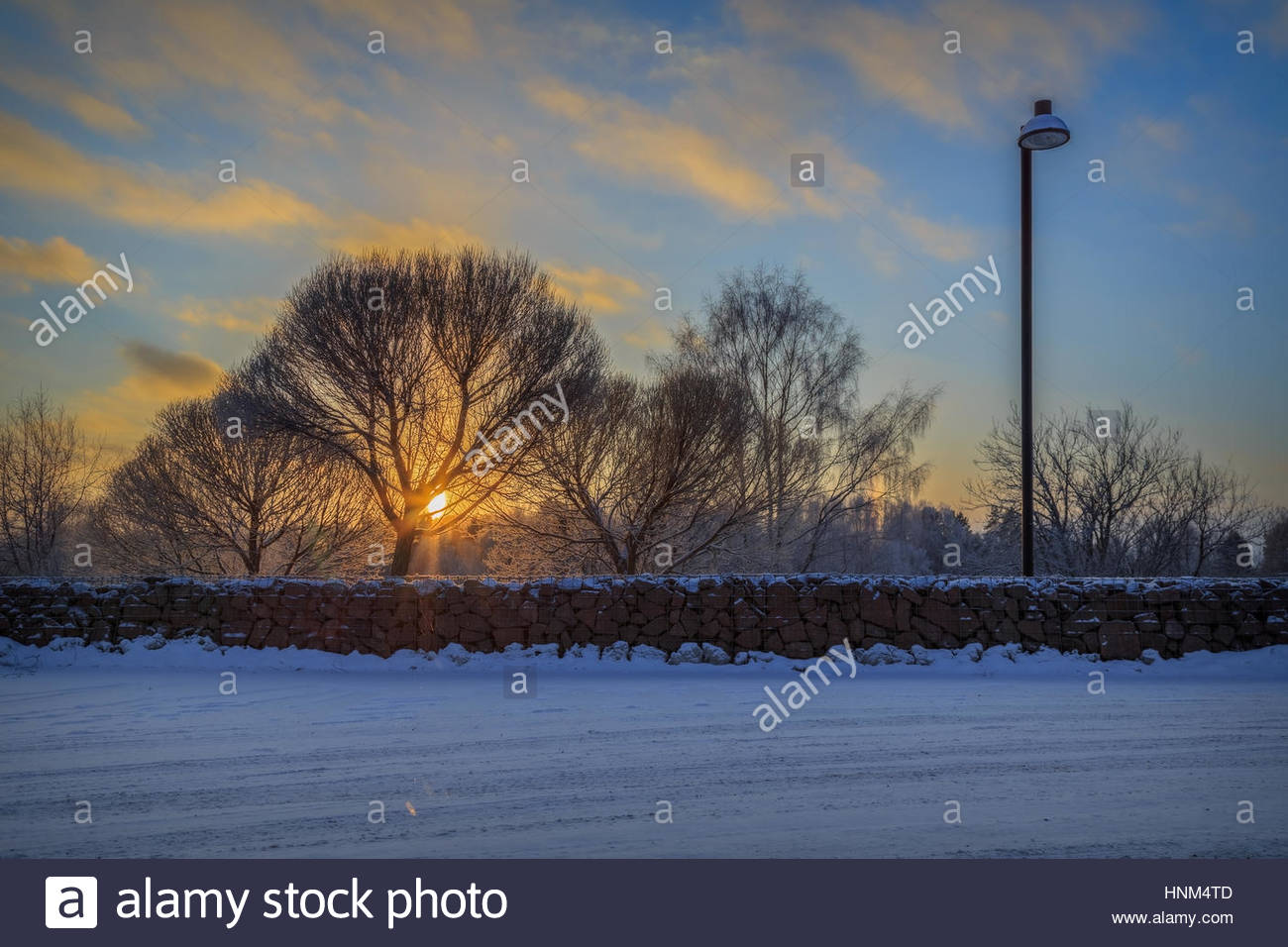 winter,street,  landscape with rock wall, lantarn and trees during sunset Stock Photo