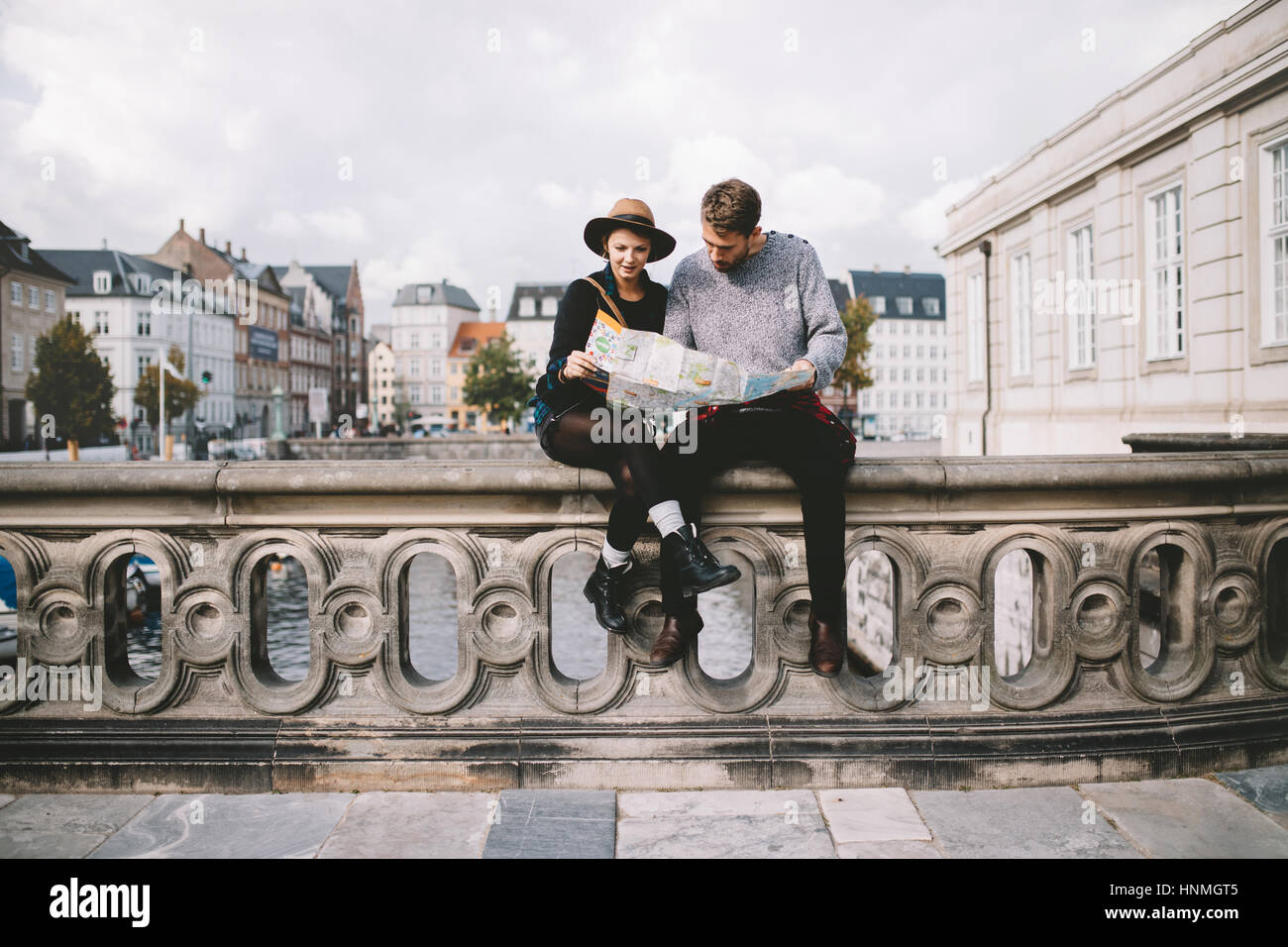 Young couple looking at a navigation map sitting on a river bridge. Tourists exploring the area on cloudy day. - Stock Image