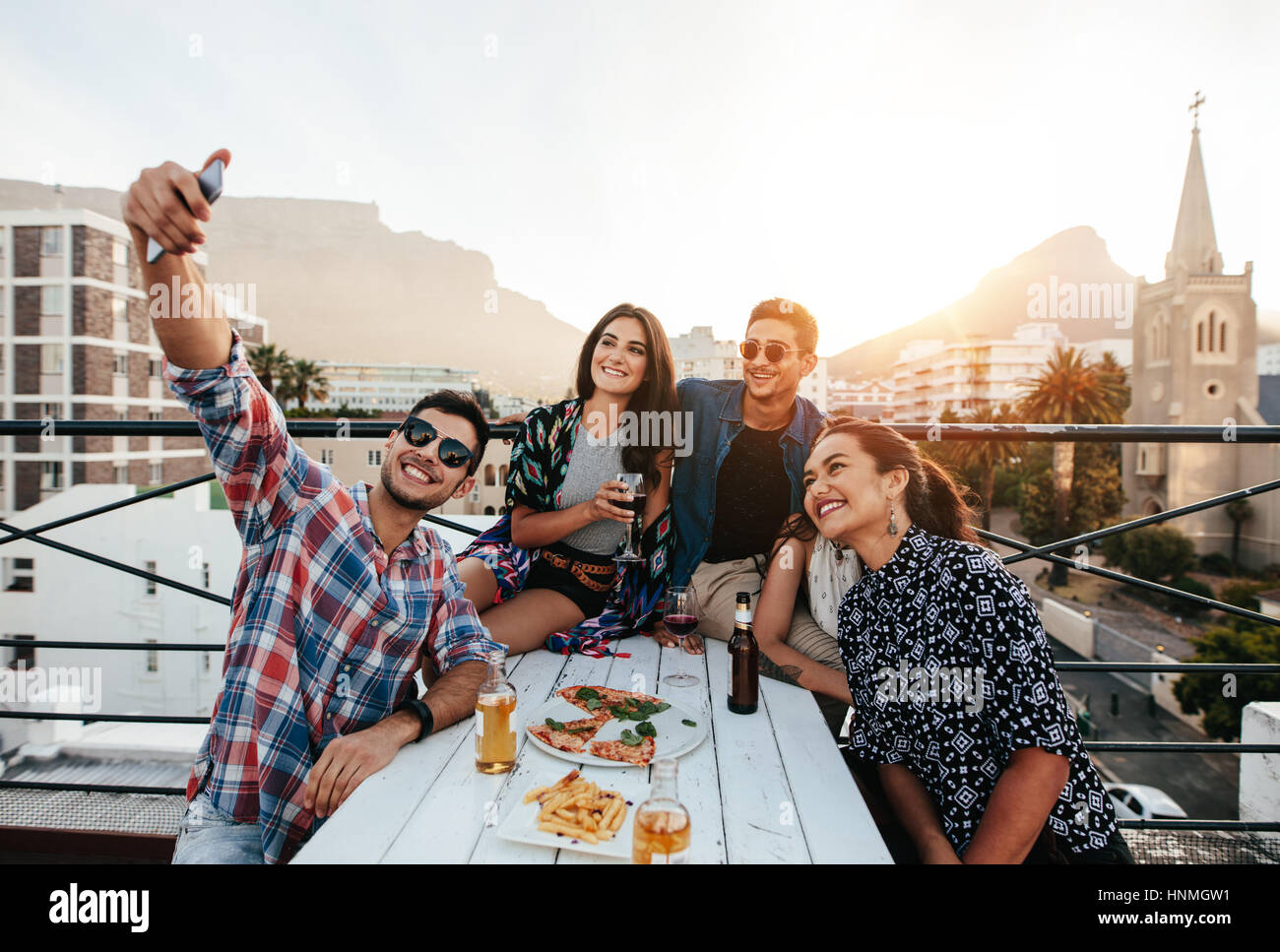 Group of friends having a party on the rooftop making a selfie. Happy young people taking self portrait during party. - Stock Image