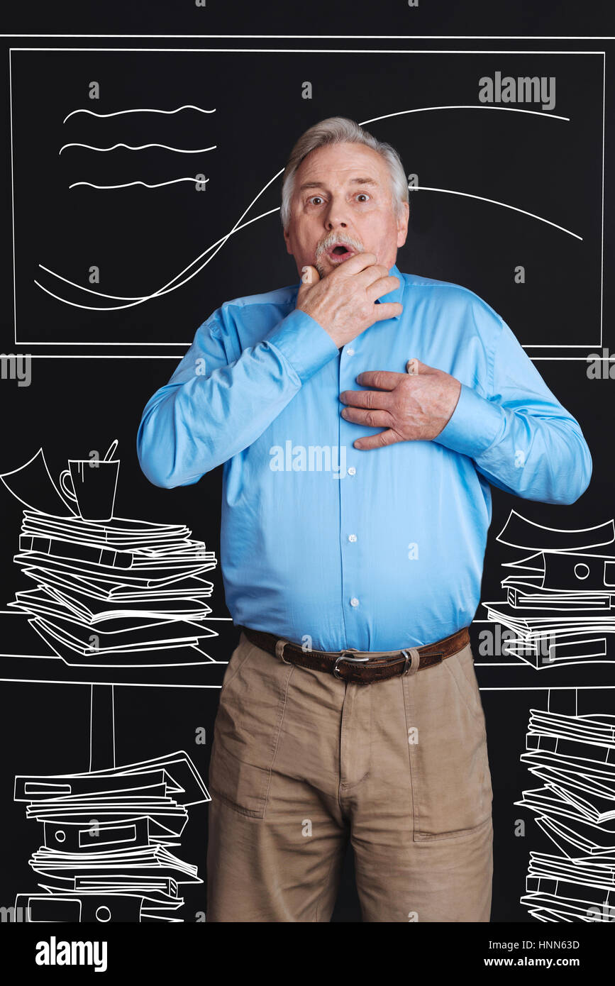 Nice aging man standing among piles of paper - Stock Image