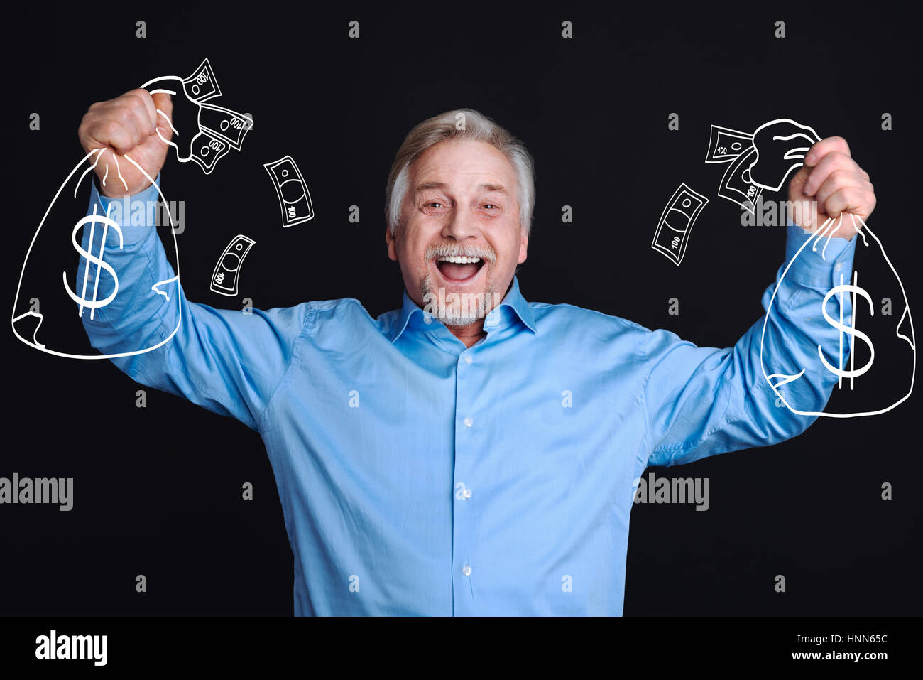 Delighted positive man standing against the black background - Stock Image