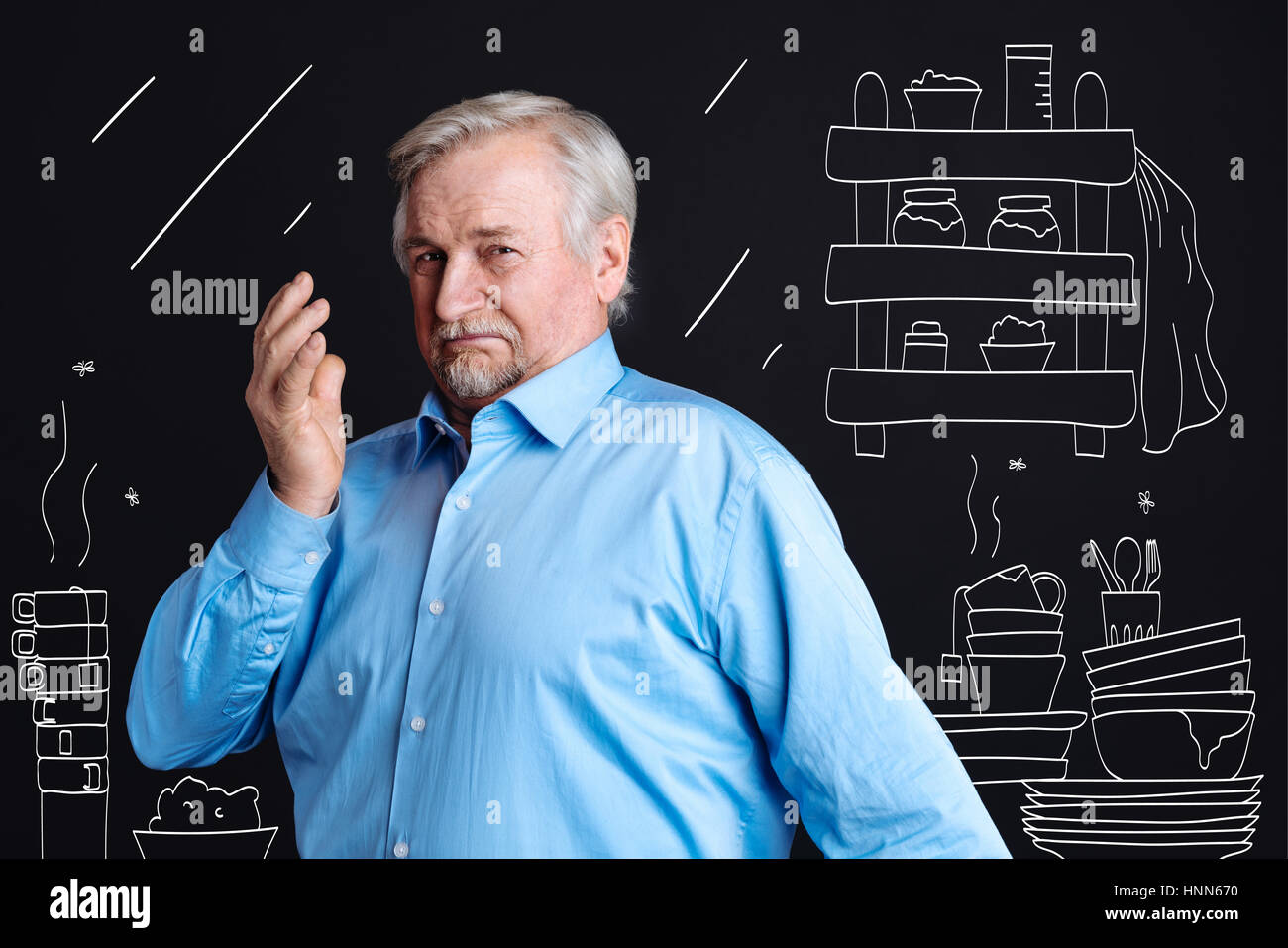 Cheerless aged man standing in the dirty kitchen - Stock Image