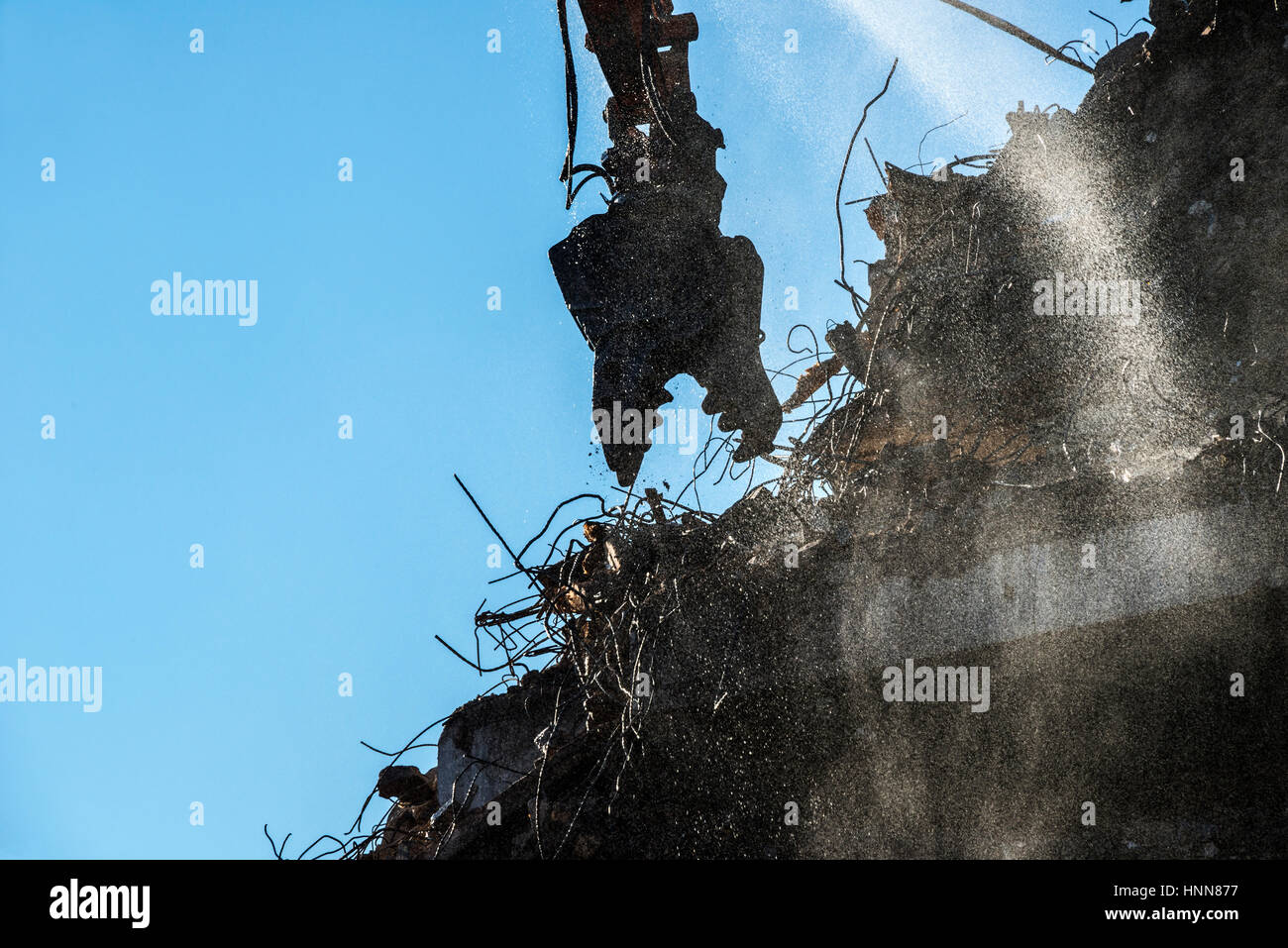 Jaws of High Reach Excavator Tearing Down Building - Stock Image