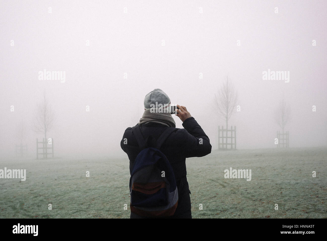 Young man in winter coat, hat and scarf taking photos with his mobile phone of London park, disappearing in the Stock Photo