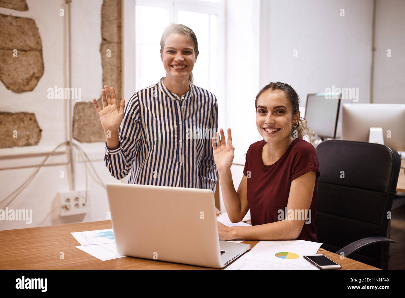 Two young business women smiling big toothy smiles and waving at the camera while sitting at a desk with a laptop - Stock Image