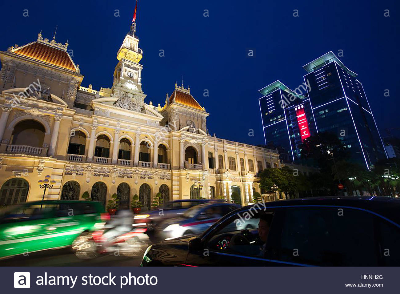 Fast paced traffic and quickly built office towers hem in the historic Ho Chi Minh City Hall. - Stock Image