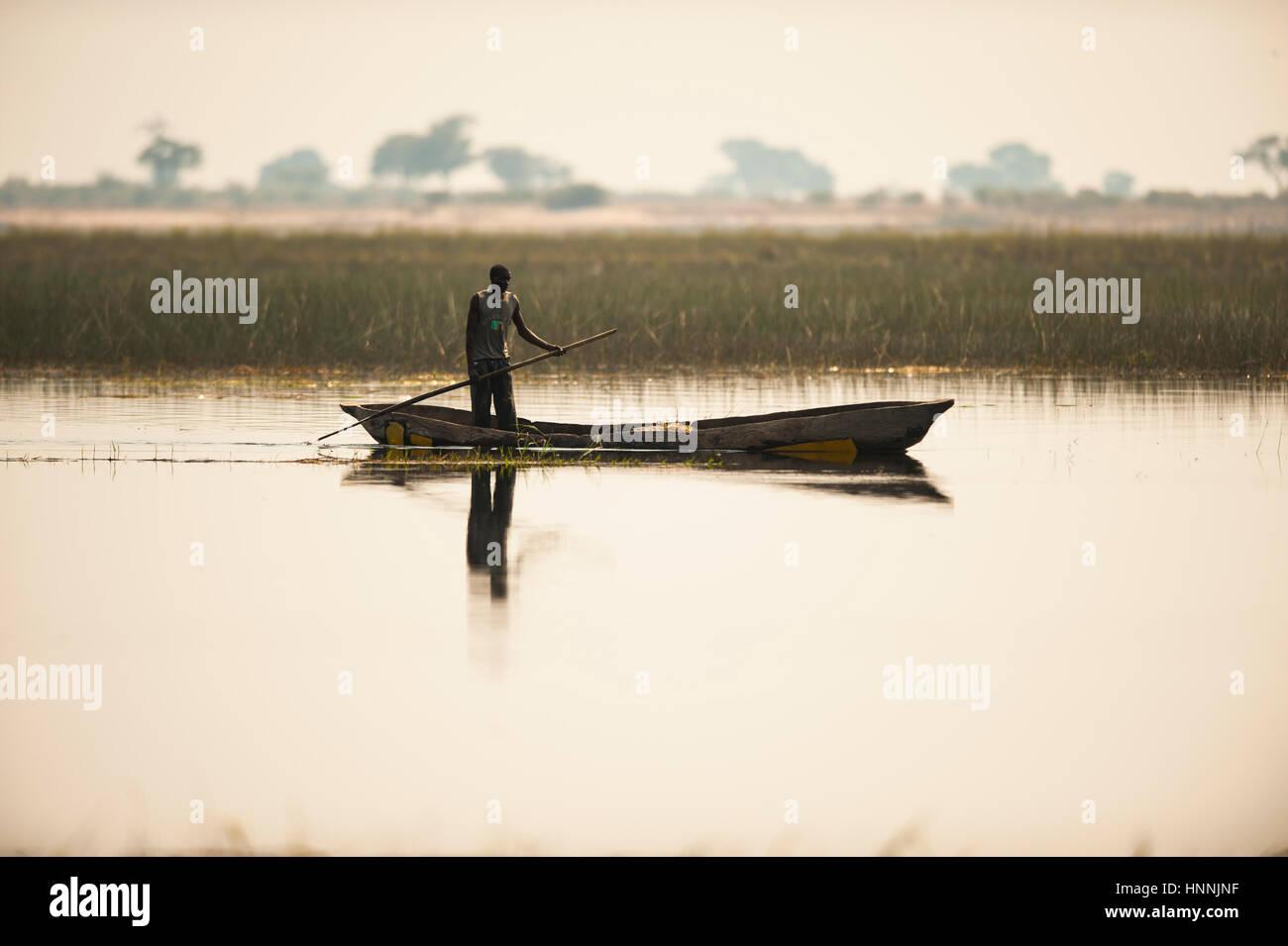 Namibian fisherman and traditional dug-out canoe - Stock Image