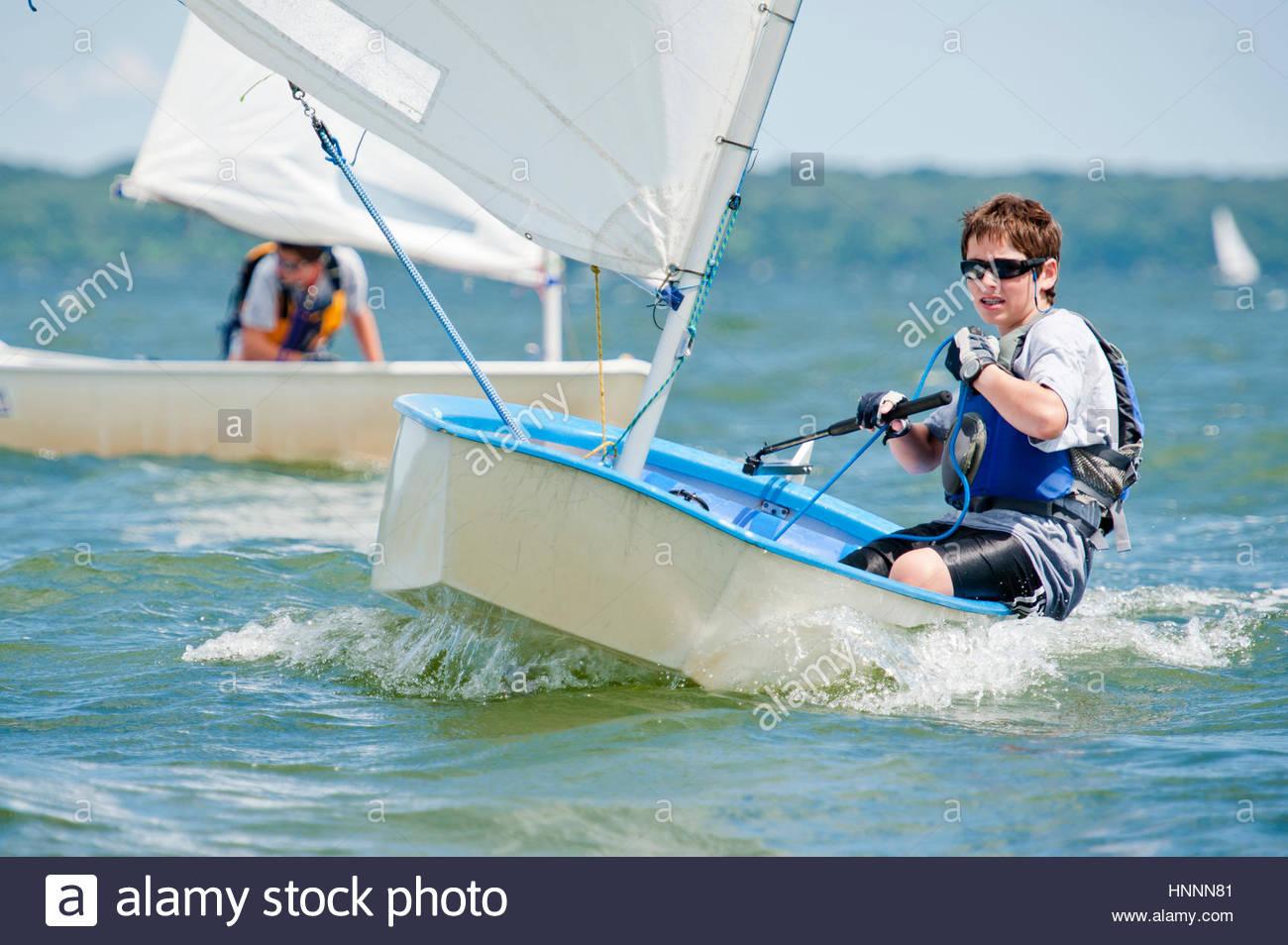 Boy sailing sailboat at sea - Stock Image