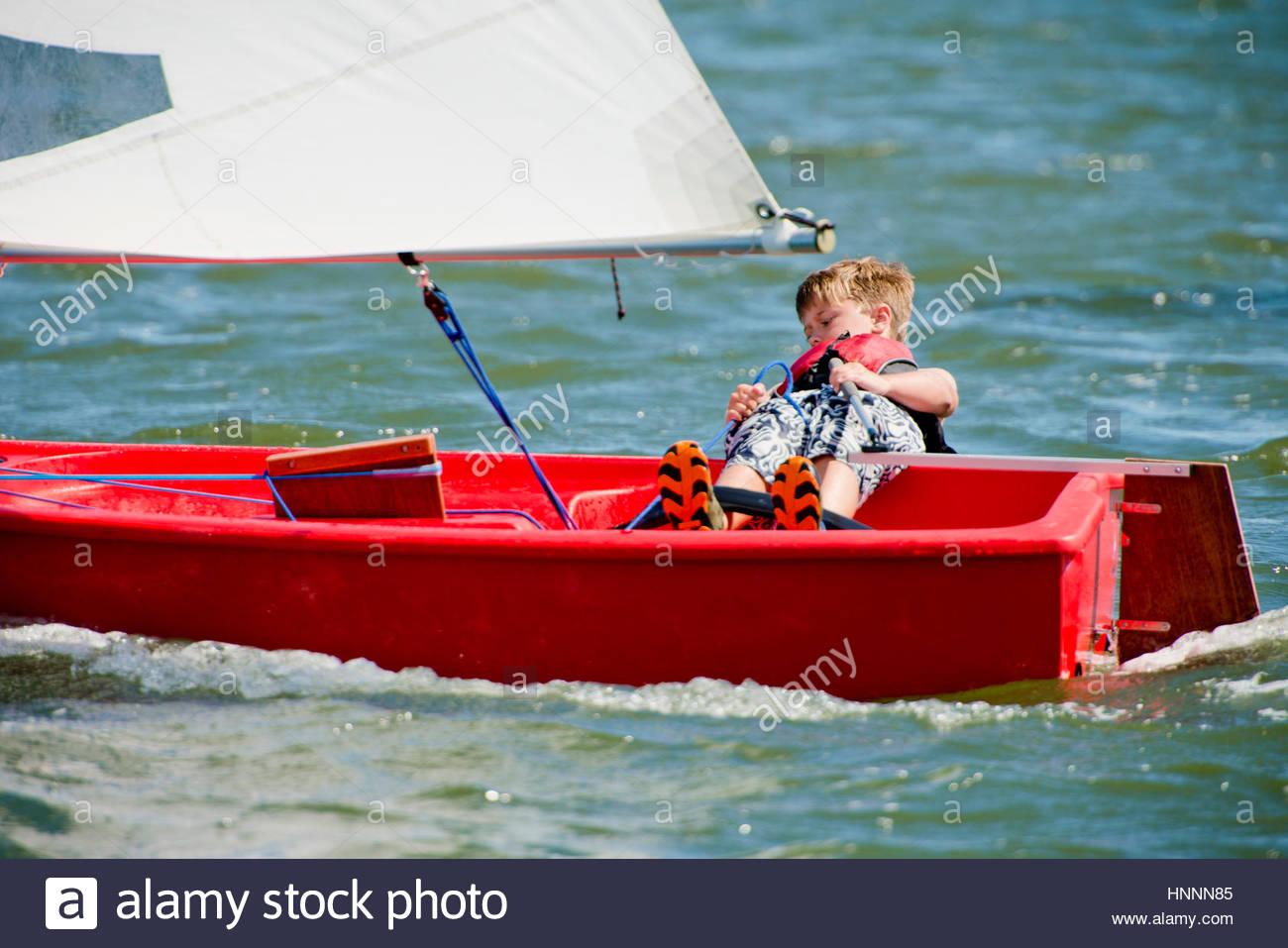 Boy controlling sailboat at sea - Stock Image