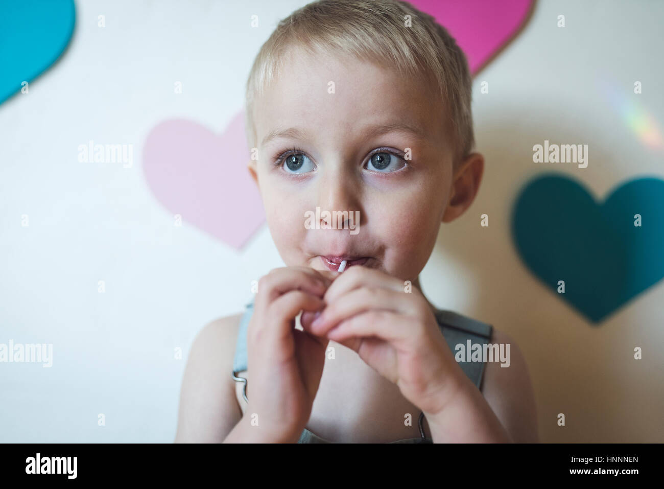Cute boy looking away while sucking lollypop at home - Stock Image