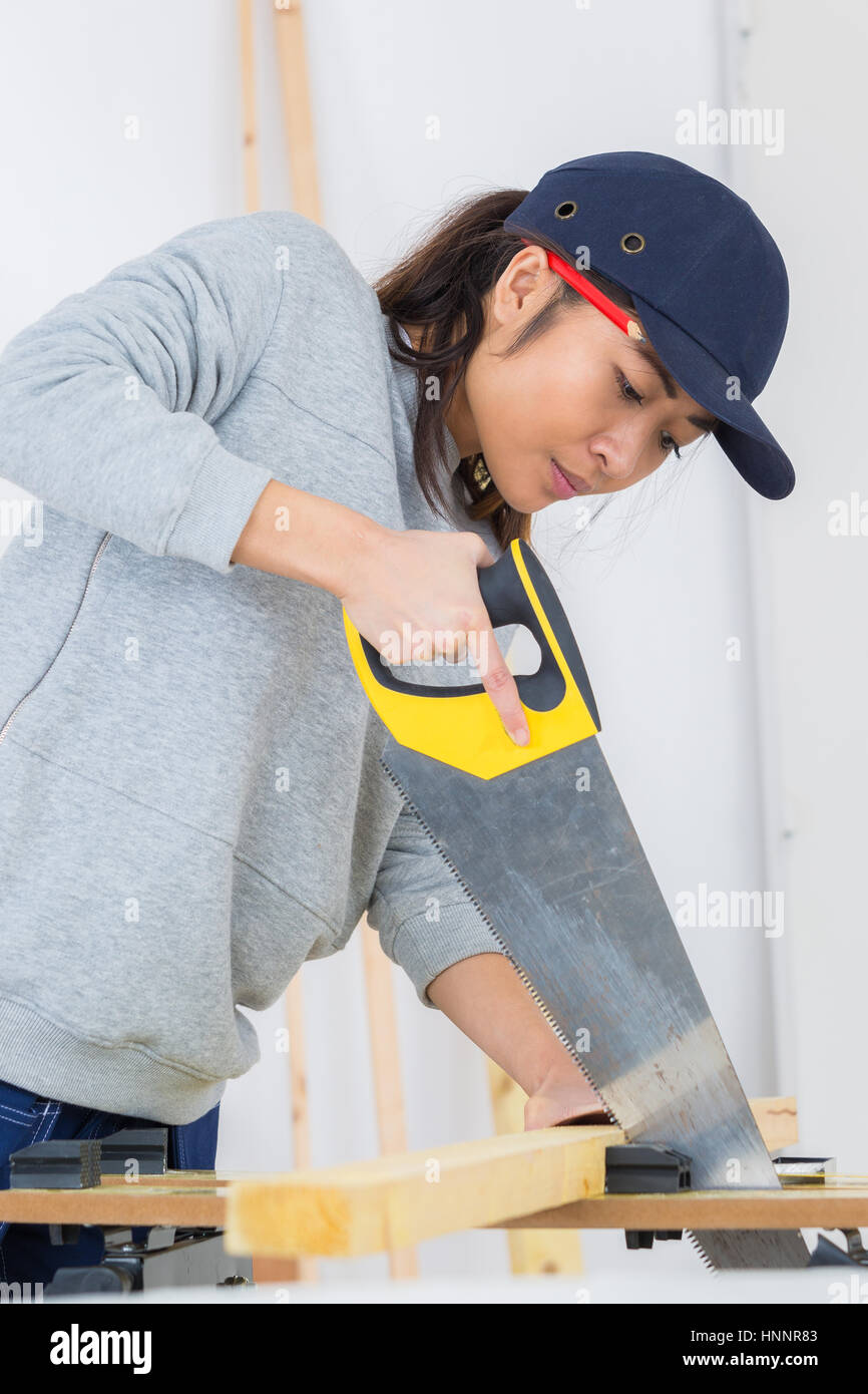 Female contractor using handsaw - Stock Image