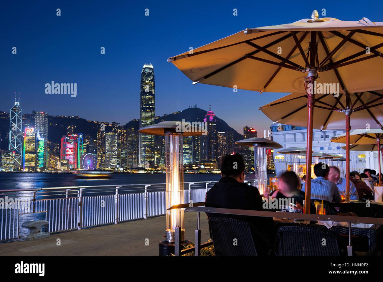 Outdoor restaurant facing the Hong Kong skyline, Hong Kong, China. - Stock Image
