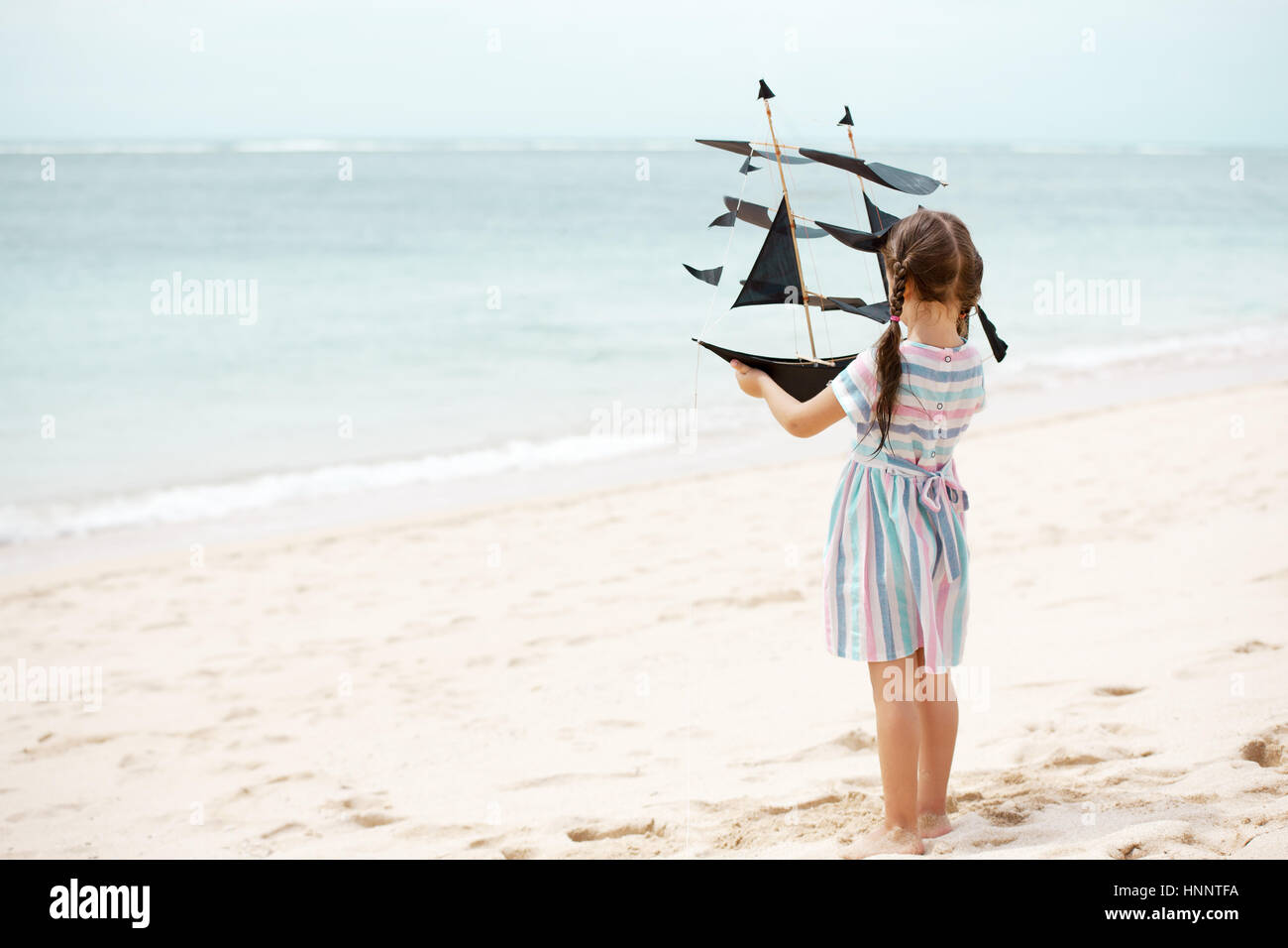 Cute little girl playing on the beach flying ship kite. Child enjoying summer family vacation at the sea. - Stock Image