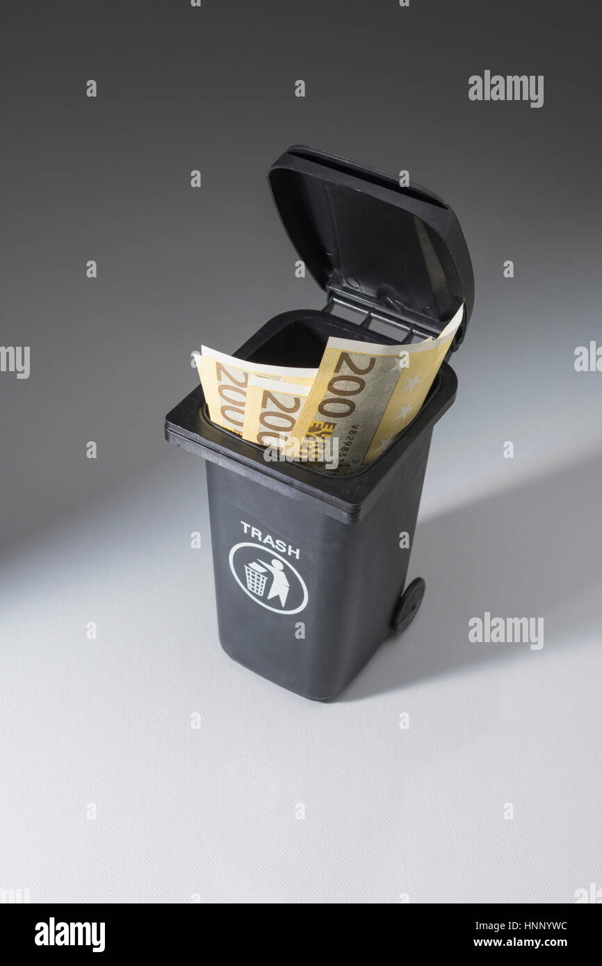 200 Euro banknotes / bills in a toy wheely bin / wheeliebin / trash bin. Metaphor for wasting money. - Stock Image