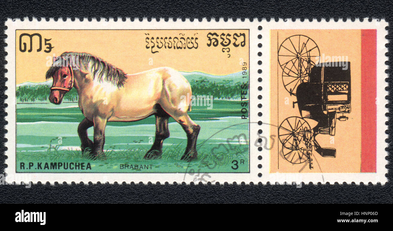 A postage stamp printed in R.P. Kampuchea  shows  a Brabant, draught horse and coach 1989 - Stock Image