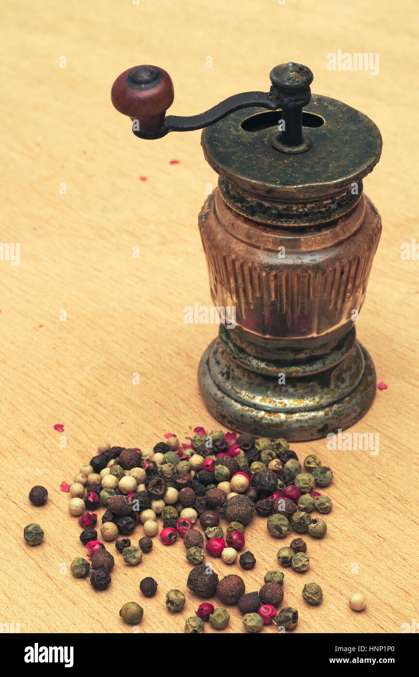 Old pepper grinder and peppercorns - Stock Image