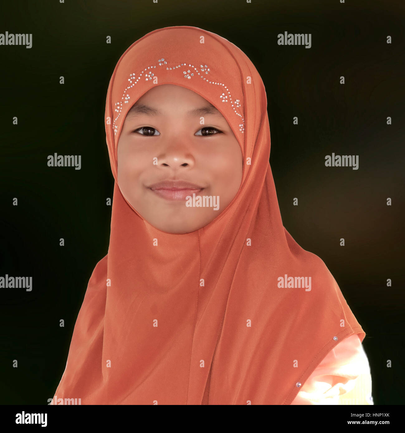 Portrait of a young Muslim child wearing a hijab. Girl Khimar. Plain background. Thailand people, Southeast Asia - Stock Image