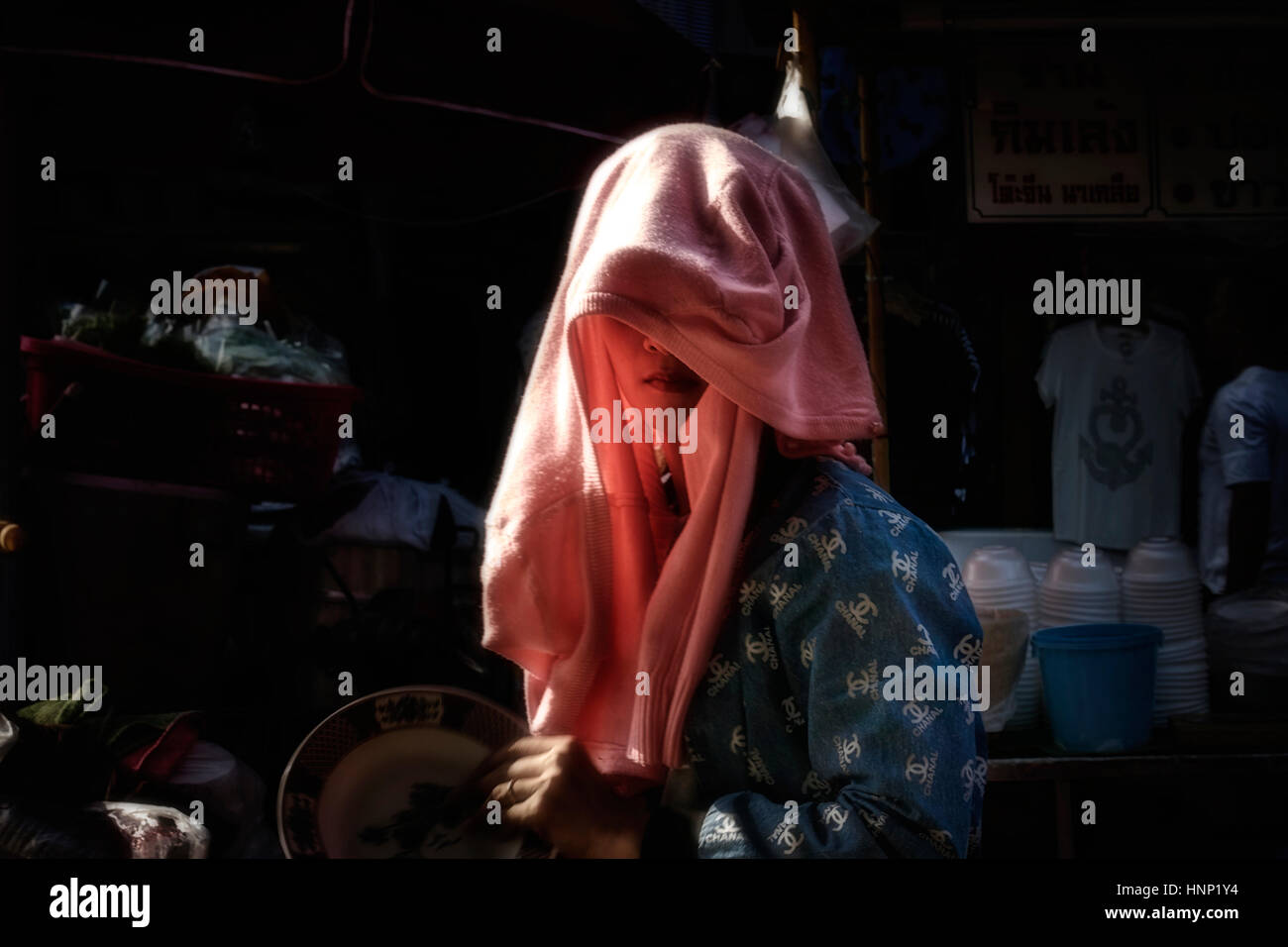 Thailand mystery woman adapting clothing as a sunshade and face sun protection. People Southeast Asia - Stock Image
