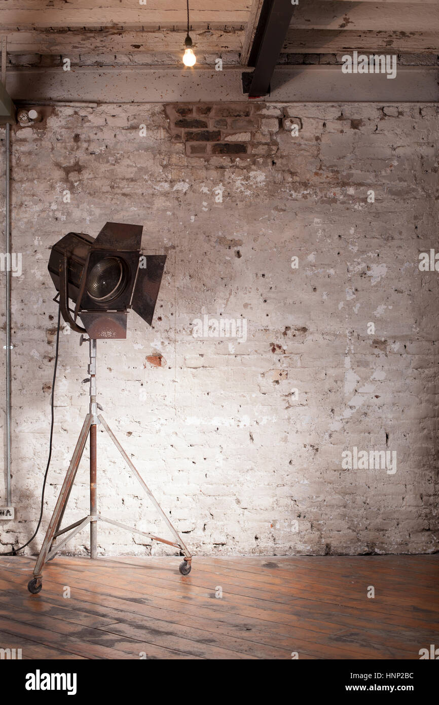 A vintage Hollywood studio light with a distressed brick wall and wooden floors. - Stock Image
